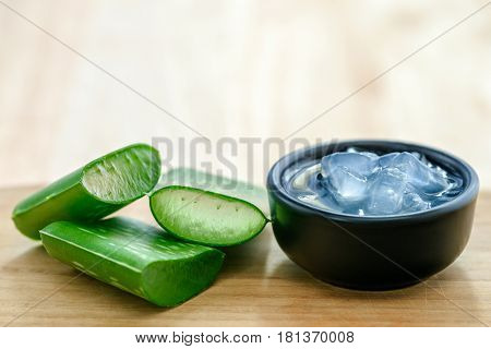 Aloe vera juice in bowl with fresh aloe vera leaves on wooden background