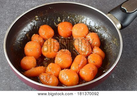 Honey glazed baby carrots with sea salt and thyme in a frying pan on a grey abstract background. Healthy eating concept. Fastening food. Healthy meal