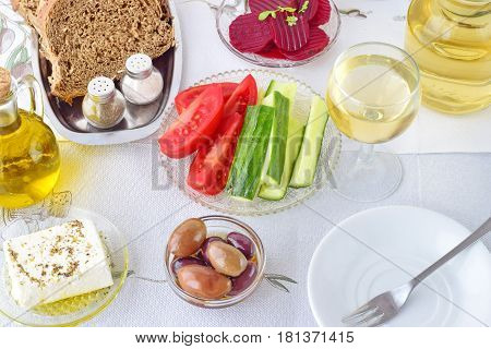 Greek food mezedes. Jars with olive oil and vine vinegar olivesfeta tzatziki dark bread raki beetroot fresh cucumber and tomato on a white background. Healthy eating concept. Healthy food