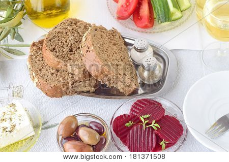 Greek food mezedes. Jars with olive oil and wine vinegar olives feta tzatziki dark bread raki beetroot fresh cucumber and tomato on a white background. Healthy eating concept. Healthy food