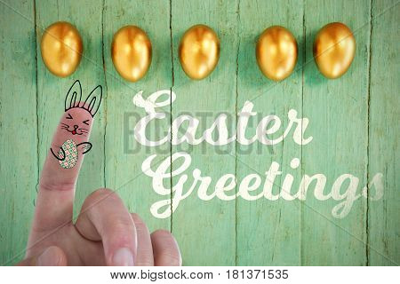 Digitally composite image of fingers representing Easter bunny against golden easter eggs arranged on wooden surface