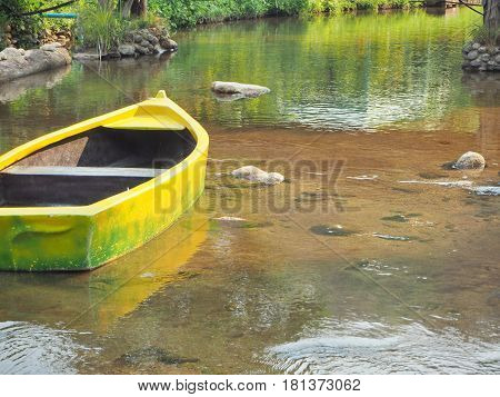 A yellow Canoe in the lake clear water see through the sand