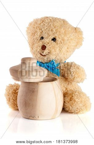 Toy teddy bear with wooden barrel isolated on white background.
