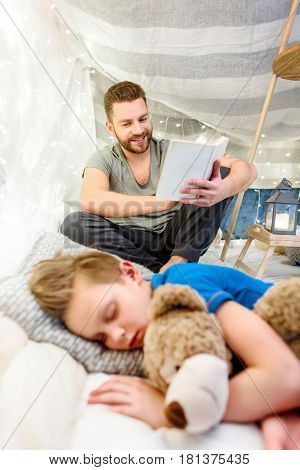 Smiling Father Reading Book To Cute Little Boy Sleeping With Teddy Bear