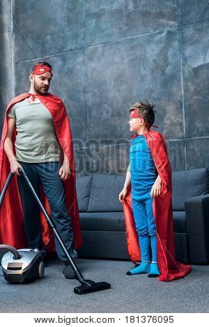 Father And Son In Red Superhero Costumes Vacuuming Carpet