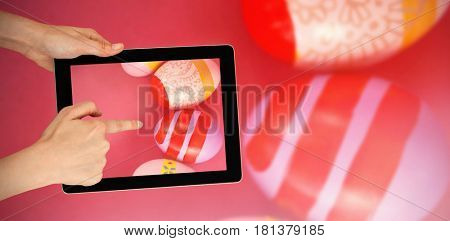 Hands touching digital tablet against white background against various easter eggs arranged on pink background