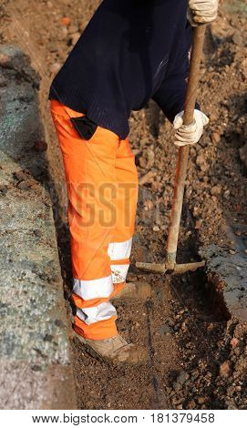 Worker With The Shovel Inside At Trench In The Roadwork