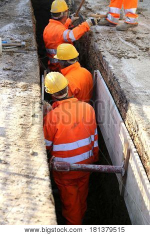 Workers With Yellow Helmet Inside The Trench Of Road Constructio
