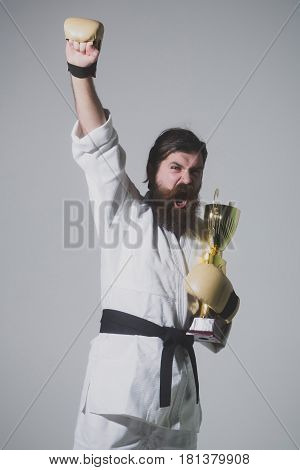 bearded karate man long beard brutal caucasian hipster with moustache in white kimono with black belt and boxing gloves with shouting happy face holds gold champion cup on grey background unshaven guy