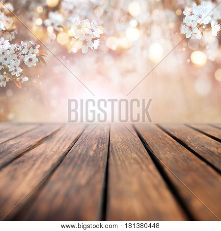 Cherry blossoms in spring with sunrays and bokeh in front of an empty wooden table for a concept
