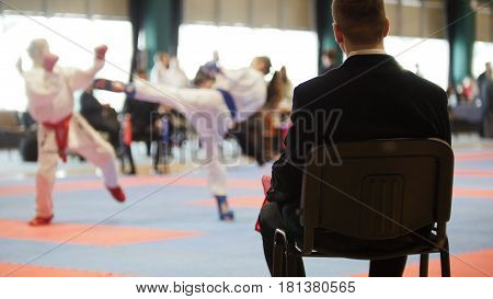 Martial art competitions- karate - judge coaches looking at female teenager's karate fighting, close up