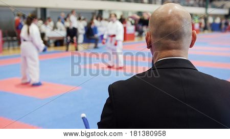 Martial art competitions - bald man coach-judge looking at karate teenager's fighting, close up