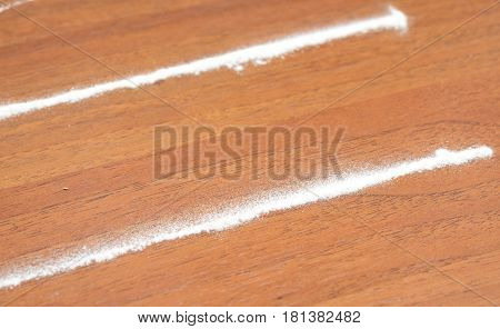 image of cocaine stripes on wooden table