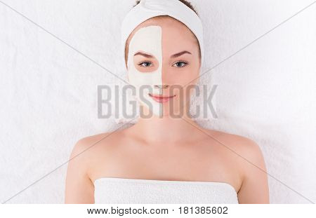 Face mask, spa beauty treatment. Woman applying facial clay mask at spa salon, skincare, top view, overhead
