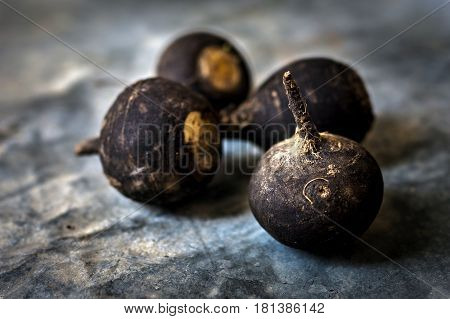 Black Radish on rustic background . . .