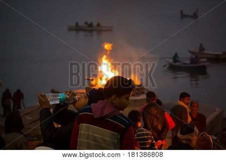 Cremation Ceremony In Manikarnika Ghat On The Ganges River In Varanasi, People Look At The Funeral P