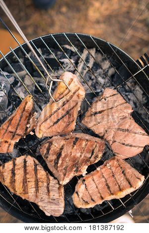 Close-up top view of grilling meat on a charcoal grill outdoors