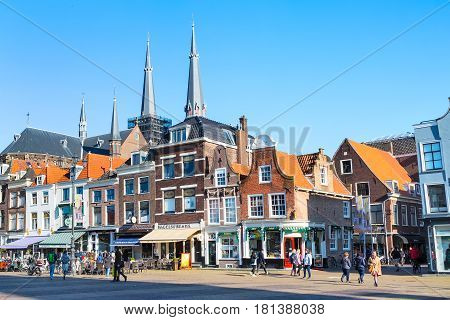 Delft, Netherlands - April 8, 2016: Street view with traditional dutch houses, church domes, bicycles, people walking in downtown of popular Holland destination