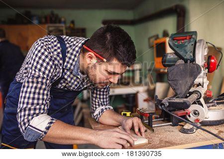 Handsome carftsman working in a work shop.