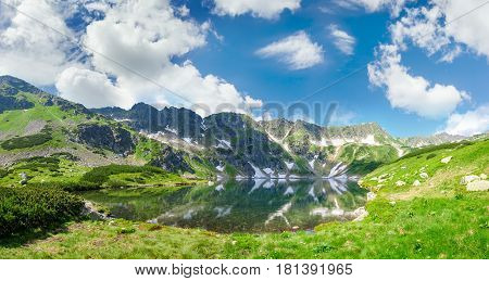 Panorama of the mountain lake with coasts overgrown with grass and mountain pine on the background of the craggy mountain slopes and sky with clouds
