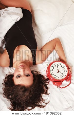 Sexy Lazy Girl Lying With Clock On Bed In Bedroom