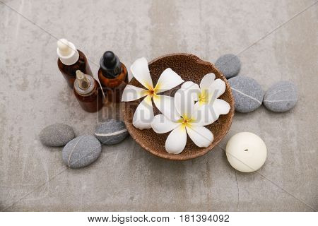 frangipani in bowl with spa stones and massage oil on grey background.
