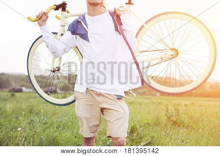 Young Man In Blank T-shirt Holding Bicycle In Green Field (intentional Sun Glare And Bright Colors)