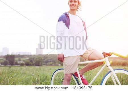 Young And Smiling Man In Blank T-shirt Sitting On His Bicycle In The Field (intentional Sun Glare An