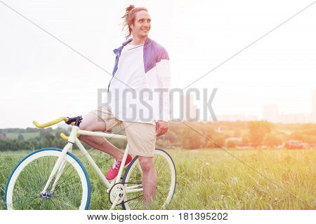 Young Long Hair Man In Blank T-shirt Sitting On His Bicycle In The Field (intentional Sun Glare And