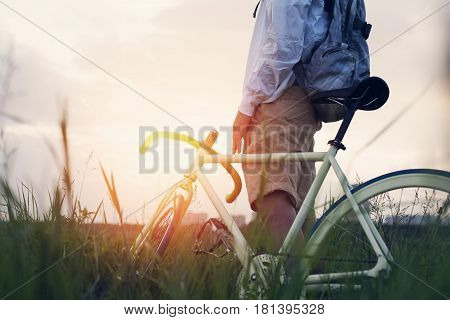 Young Man With Bicycle In The Green Field At Sunset (intentional Sun Glare And Dark Colors)