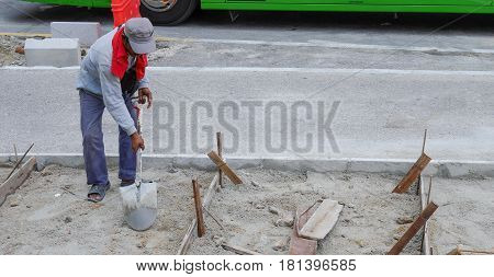 Kuala Lumpur, Malaysia - Mar 22, 2017: Unidentified Worker Working Digs A Hole With A Shovel And Spa