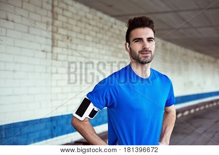Portrait Of Handsome Athlete With Stubble, Earphones And Armband