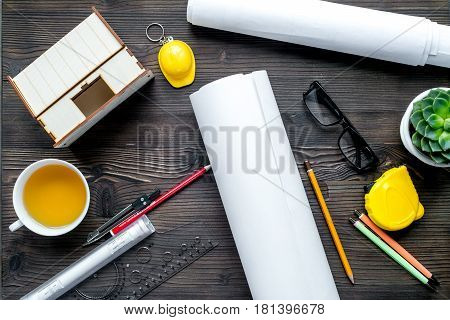 architect working desk with glasses, cup of tea, project and pencil on wooden background top view