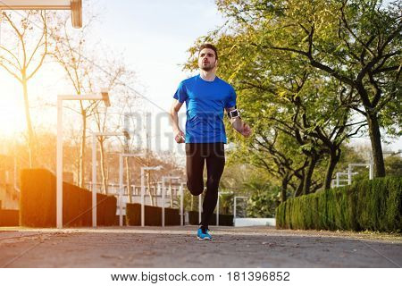 Young And Handsome Male Athlete Running In The Park (with Little Motion Blur And Intentional Sun Gla