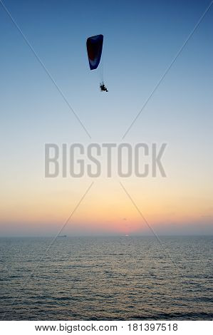 Powered paraglider flying over the sea at sunset sky background