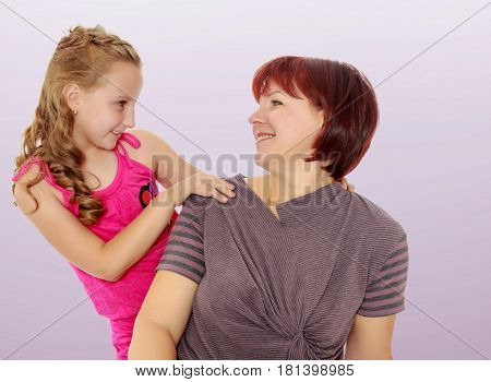 Happy family of two people, an adult mother, her beloved daughter 7 years. Daughter gently hugs the mother's neck. Close-up.Not a purple gradient background.