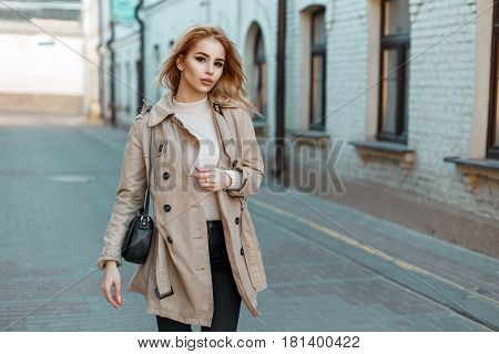 Beautiful Young Woman In A Trendy Coat With A Black Bag Walks In The City