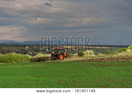 Farmer with tractor seeding crops at field in spring