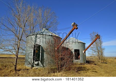 Open doored circular grain metal storage bins with augers extending are located next to railroad tracks in the springtime.
