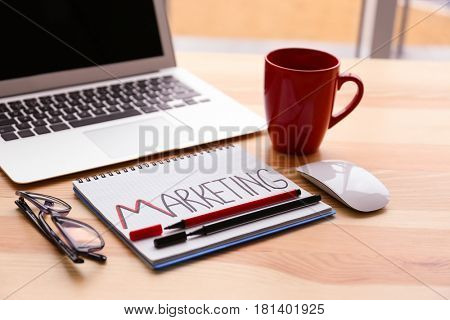 Notebook with text MARKETING on table