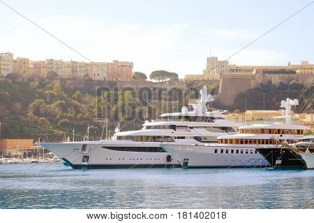 Luxury boats moored in marina in south of France with Grimaldi Royal Palace on hill in background