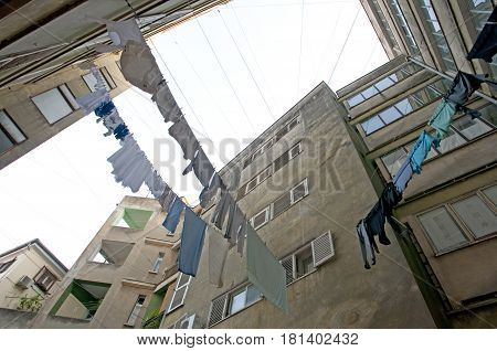 Laundry hanging from washing lines hanging in between houses