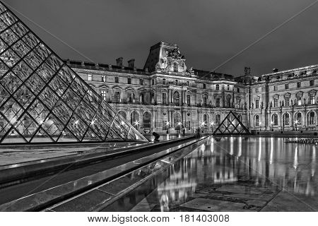 Paris, France - October 9, 2012: View of famous Louvre Museum with Louvre Pyramid at evening. A long exposed black and white photo. Louvre Museum is one of the largest and most visited museums worldwide.