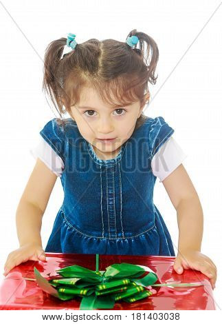 Caucasian little girl in a blue dress with short sleeves , kneeling around a red box with a bow. Close-up.Isolated on white background.