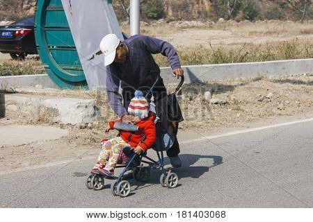 12 OCt2014 Beijing China. Chinese grandpa babysitting and take care of grandson with baby stroller on road