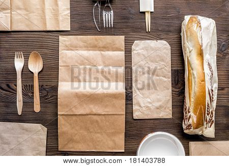 food delivery service workdesk with paper bags and sandwich on wooden background top view mock up