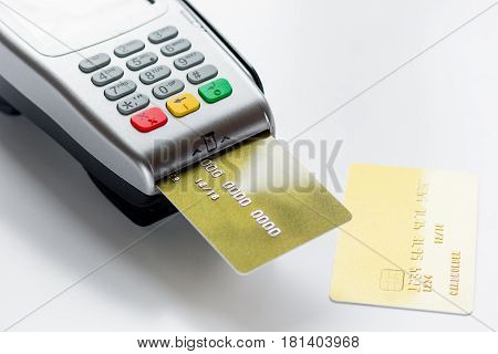 payment terminal with credit card on white table background