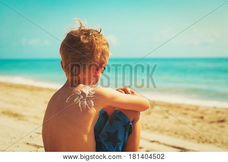 sun protection concept - little boy with suncream on shoulder at beach