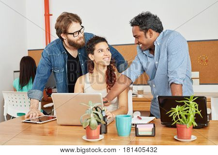 Founder and team with laptop in startup consulting agency