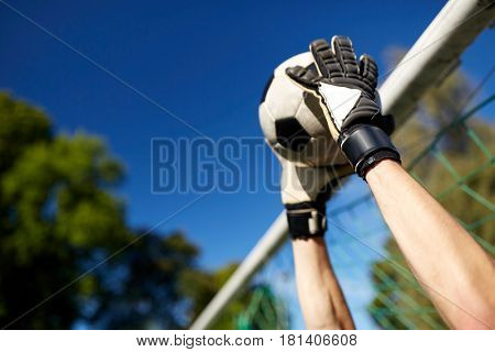sport and people - soccer player or goalkeeper hands catching ball at football goal on field